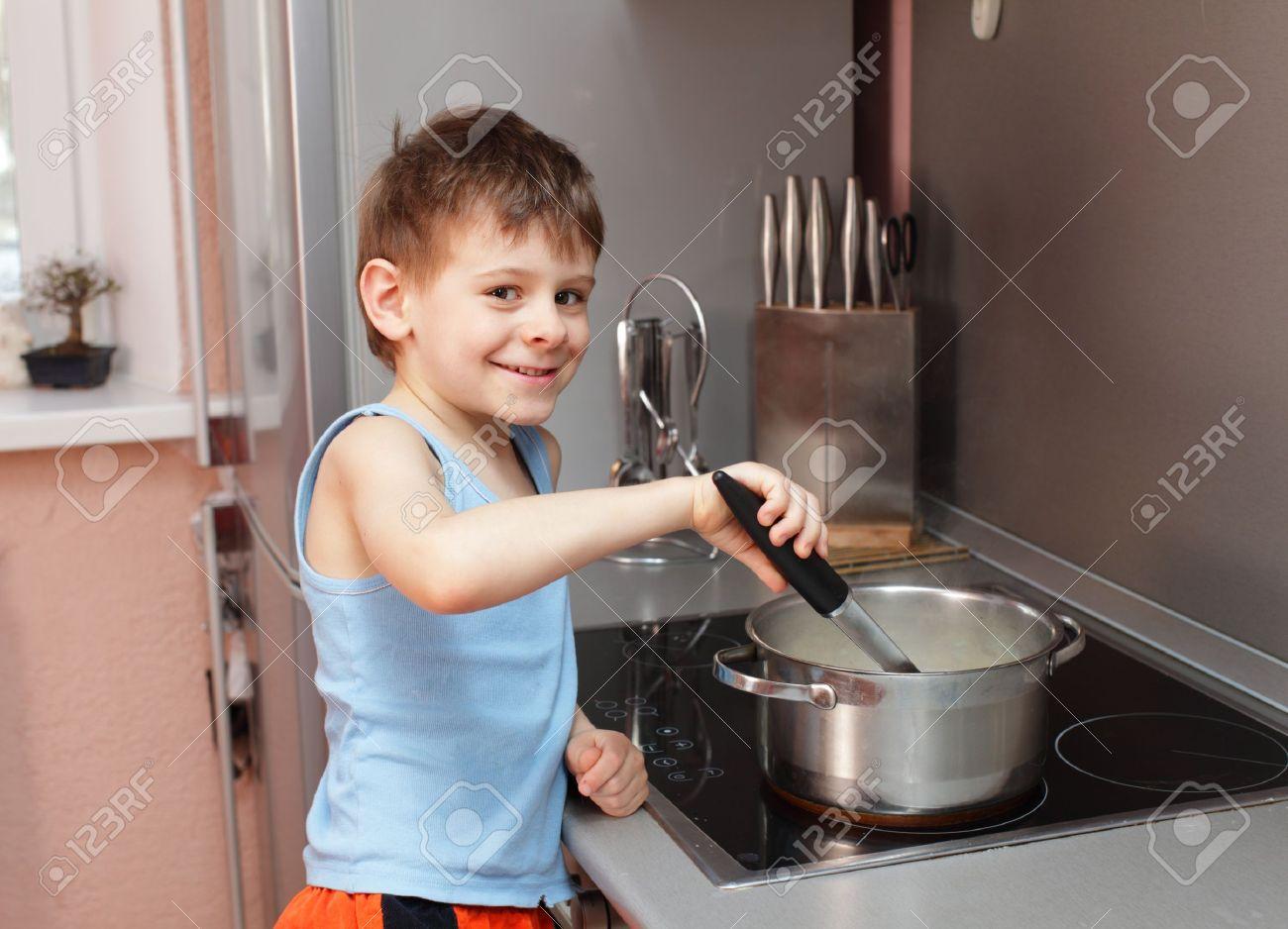 Little boy cooking porridge in kitchen Stock Photo - 10291719