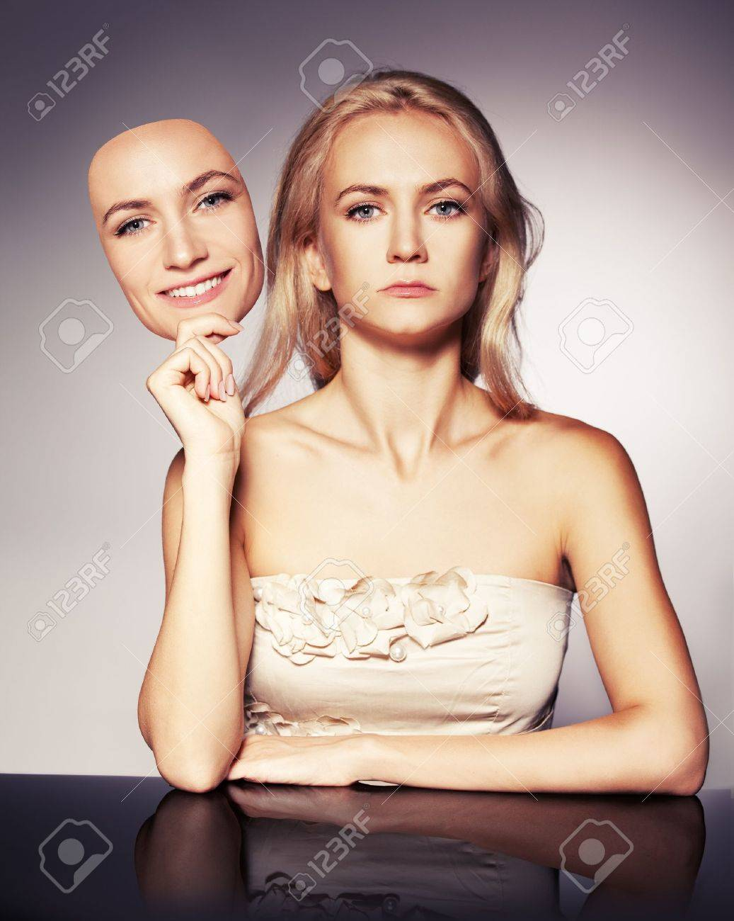 Woman hiding under the happy mask.  Hypocritical,  insincere, two-faced female Stock Photo - 14344124