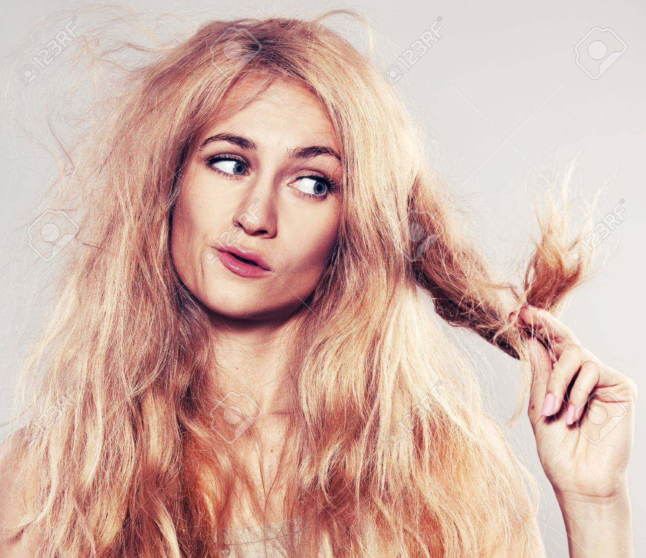 Young woman looking at split ends. Damaged long hair Stock Photo - 16491718