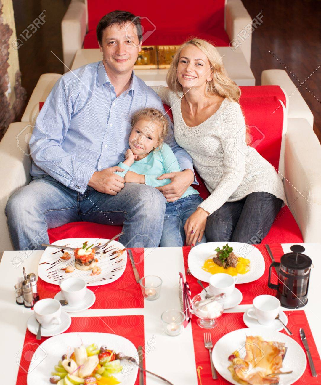 Happy Family Eating In Restaurant Mother Father And Child Cafe Stock Photo