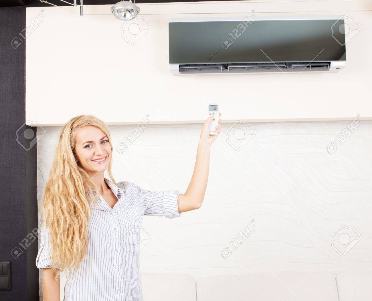 Female holding a remote control air conditioner at home Stock Photo - 19502365