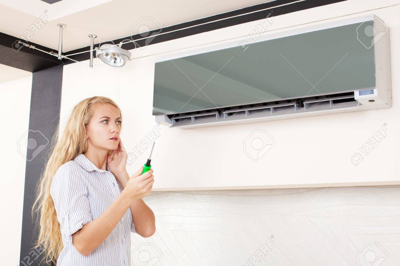 Woman looks at a broken air conditioner Stock Photo - 19502327