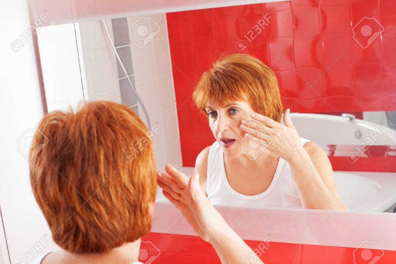 Mature woman gets cream on face in bathroom adult female looking