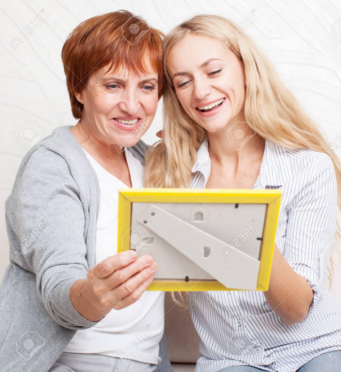 Madre Con La Hija Mirando Marco De Fotos. Mujeres Sonrientes Felices ...