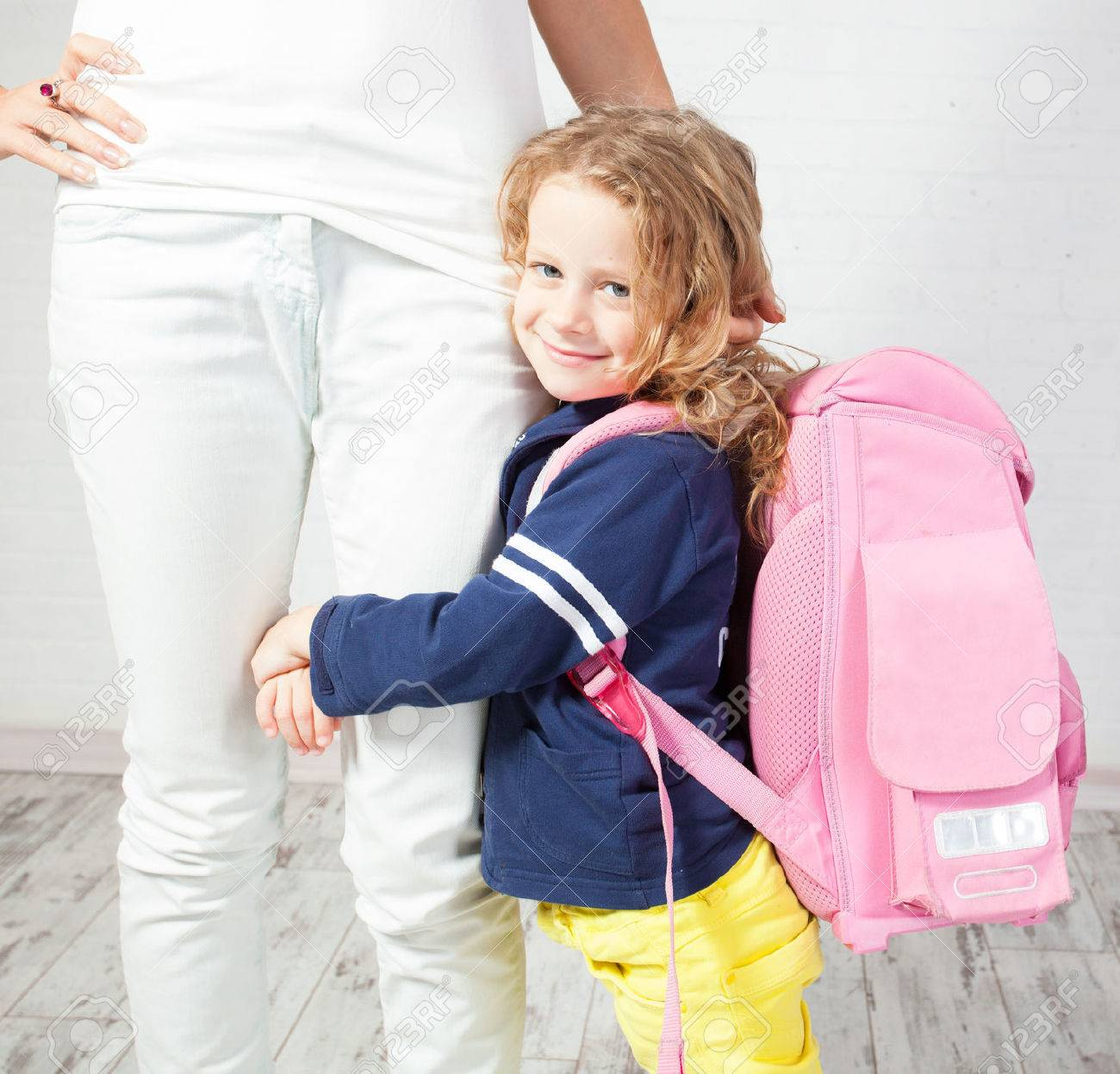 Mother helps her daughter get ready for school. Schoolgirl afraid to go to school - 46155489