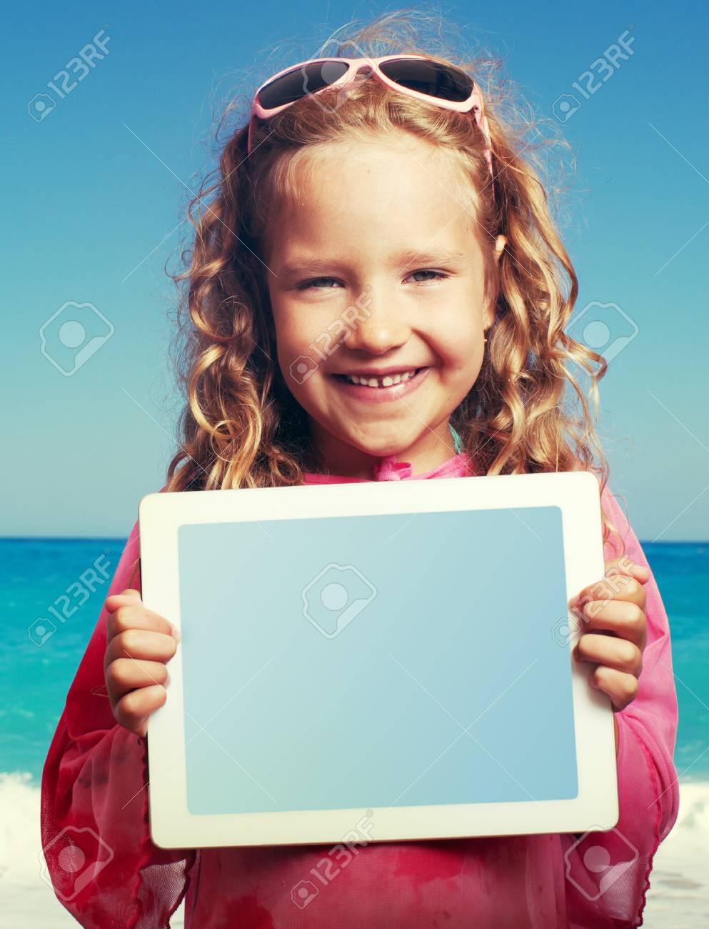 Child on the beach with tablet computer  Little happy girl showing