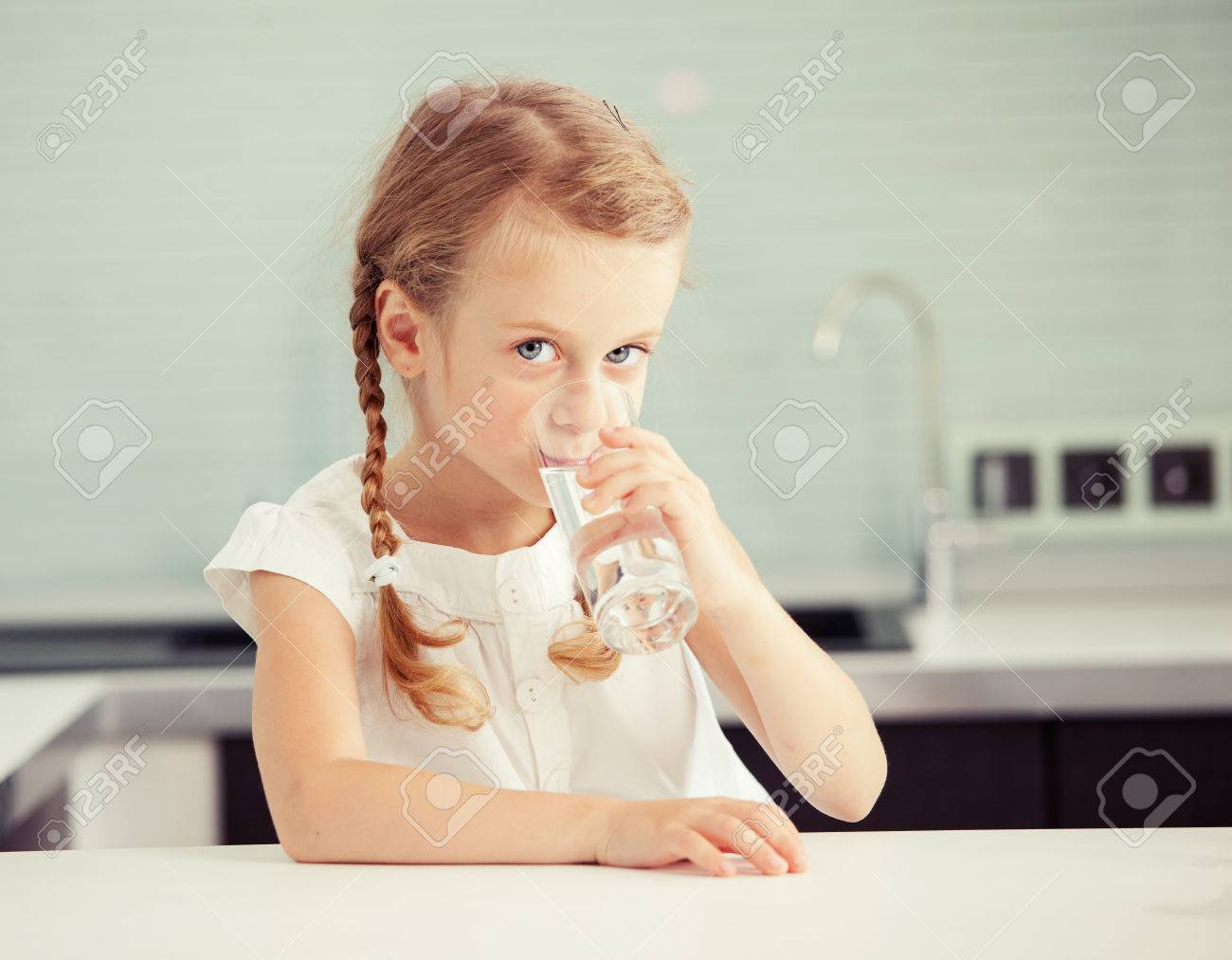 Child drinking water from glass. Happy little girl at home in kitchen - 58898527