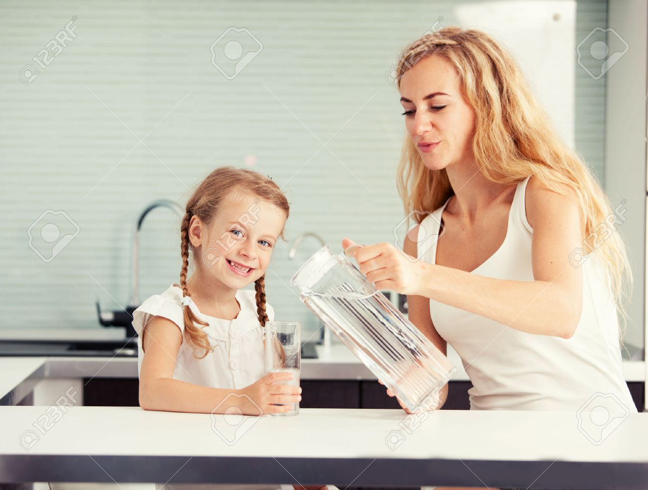 Child with mother drinking water from glass. Happy family at home in kitchen - 58898528