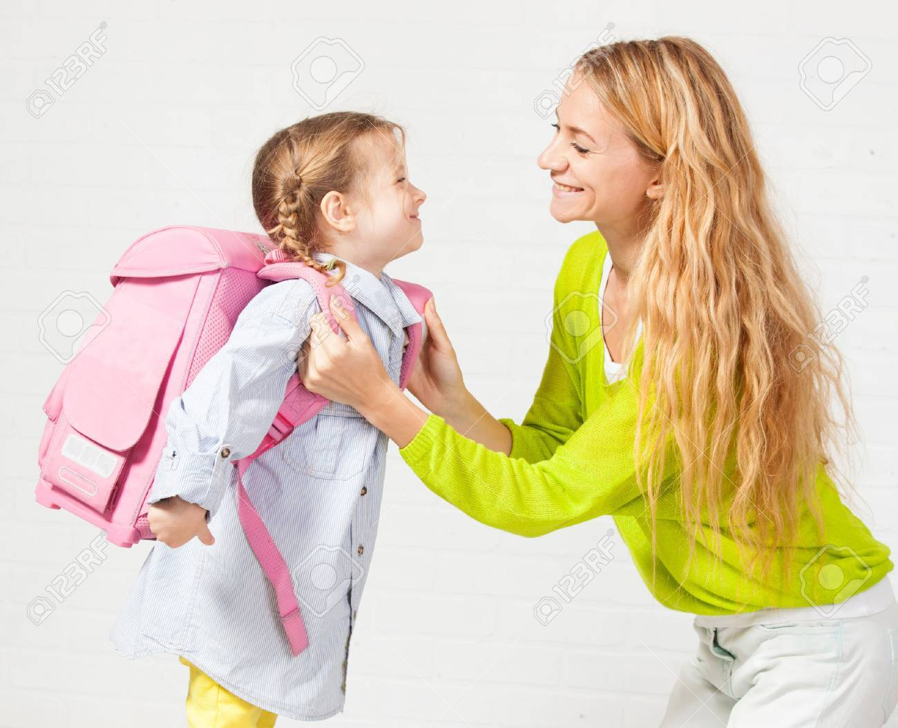 Mother helps her daughter get ready for school. Mom support child to wear a backpack - 61549155