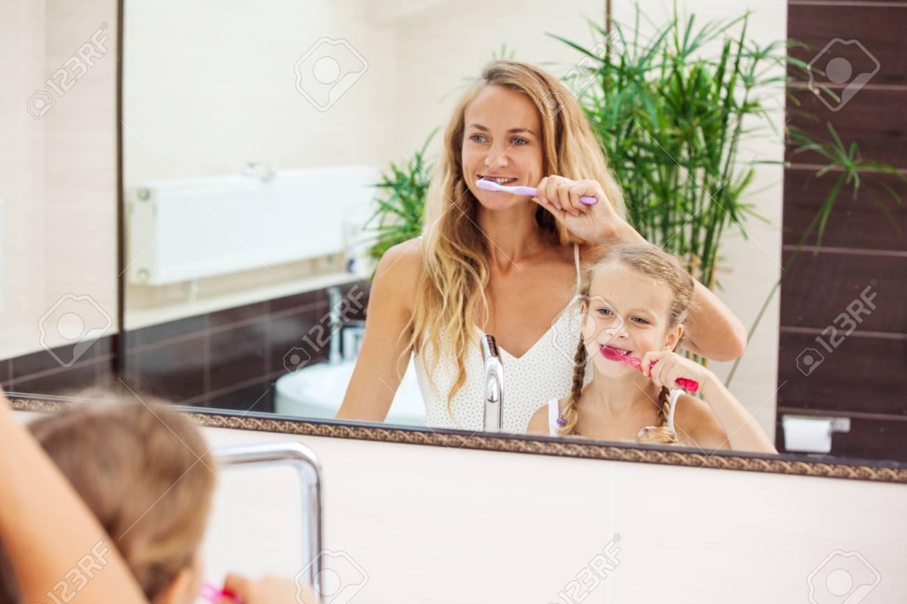 Salle De Bain Famille mère et fille se brossent les dents dans la salle de bain. famille au matin