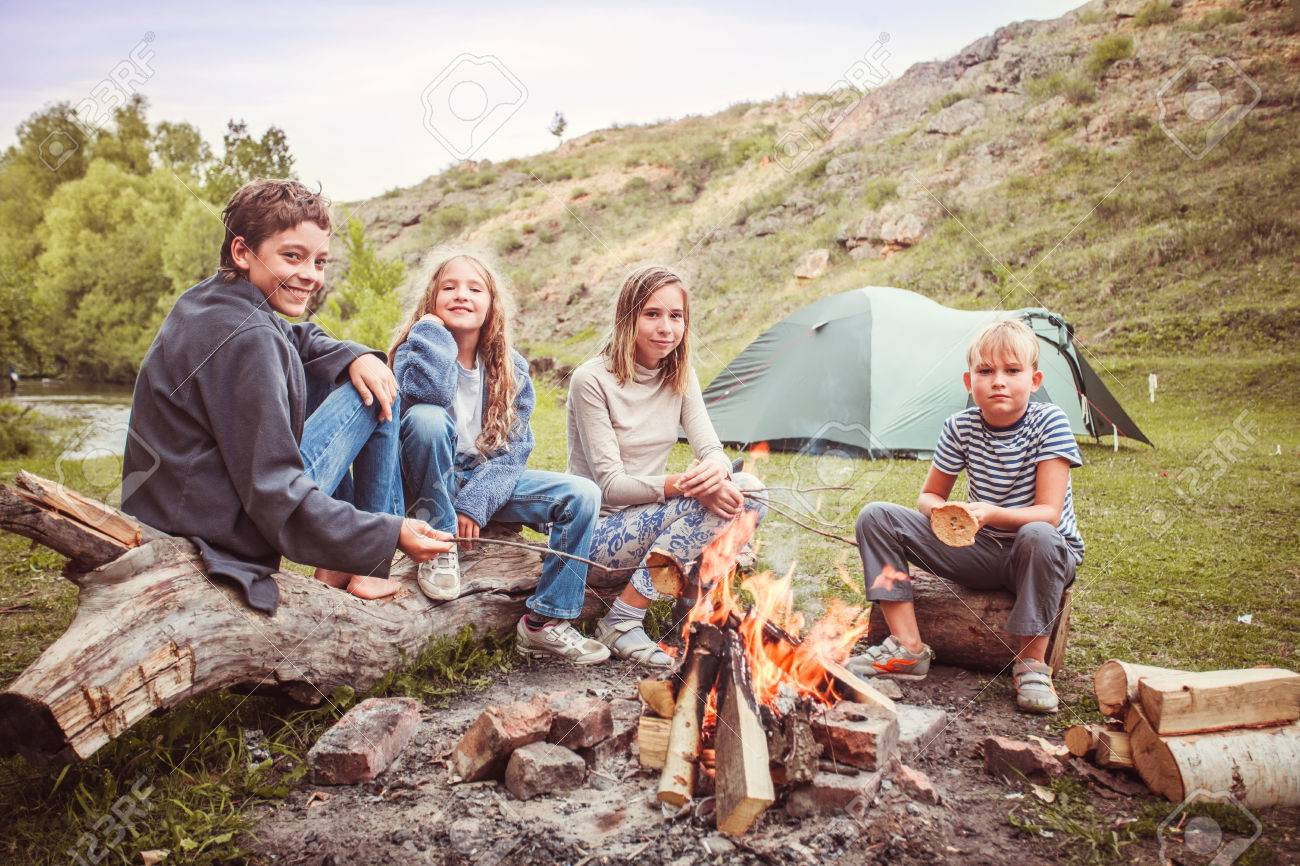Children in the camp by the fire. Group teen outdoors at summer - 75609536