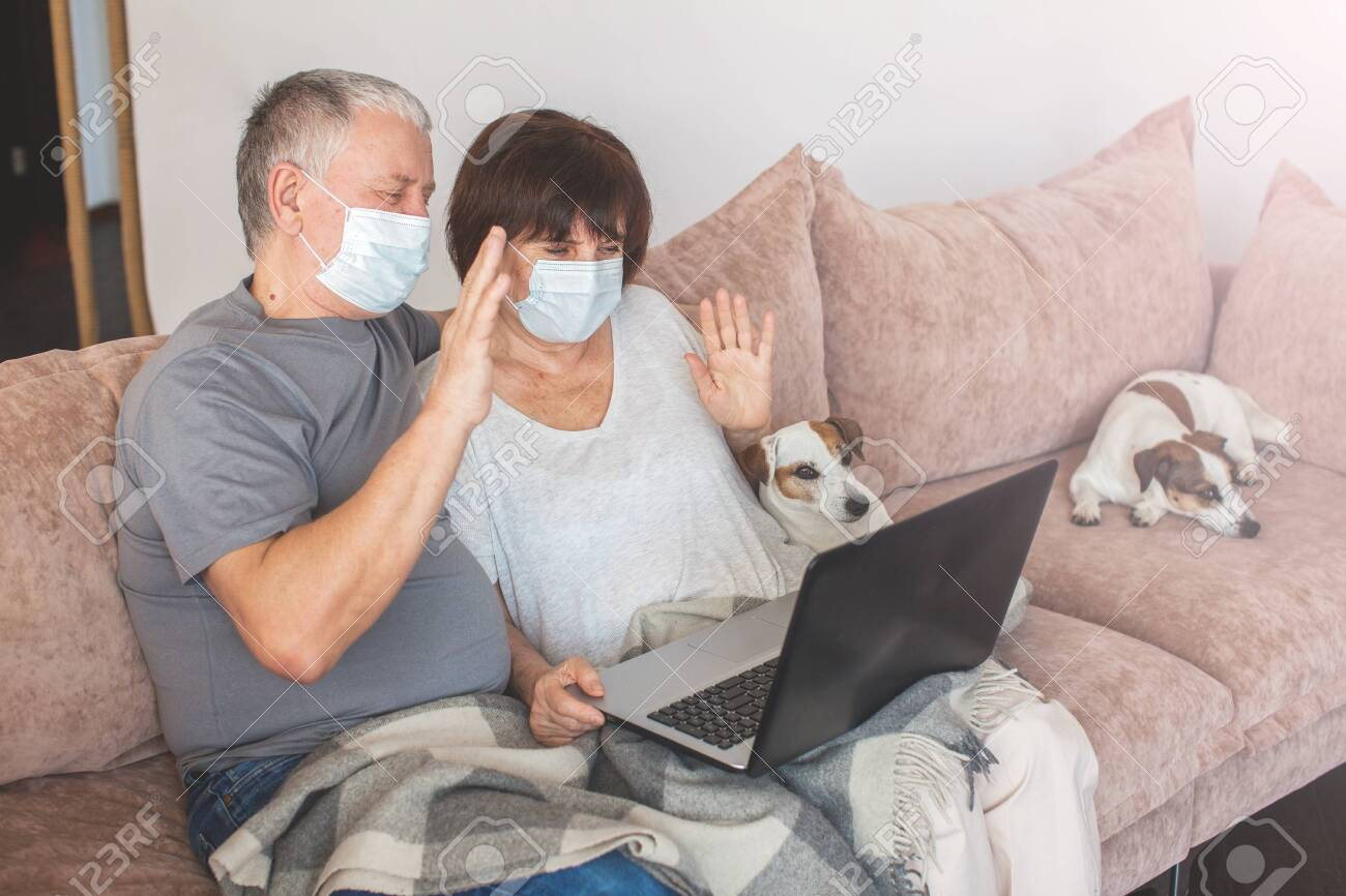 Couple old aged senior people at home with seasonal winter cold illness talking sit down on the sofa. Elderly couple in medical masks during the pandemic Coronavirus CoVid-19 - 144079865