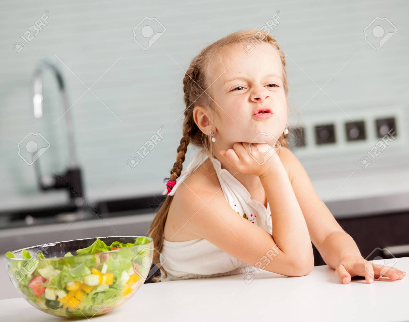 Little girl refuses to eat salad. Child looks with disgust for food - 144132026