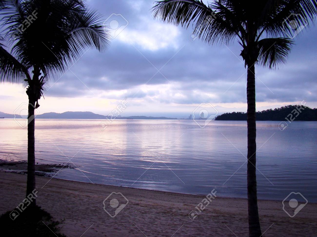 Paradise for couple - a romantic evening on the beach in a tropical exotic island. Silhouettes of two palm trees at sunset - 101448726