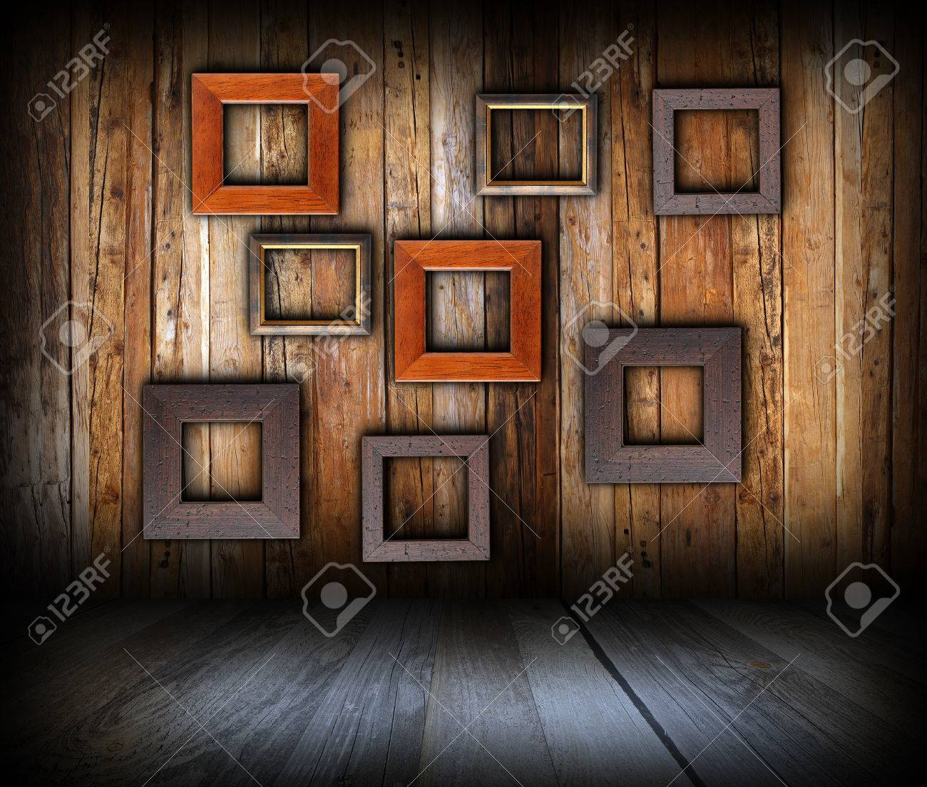stock photo wooden interior background with empty frames on wall for your message or advertising