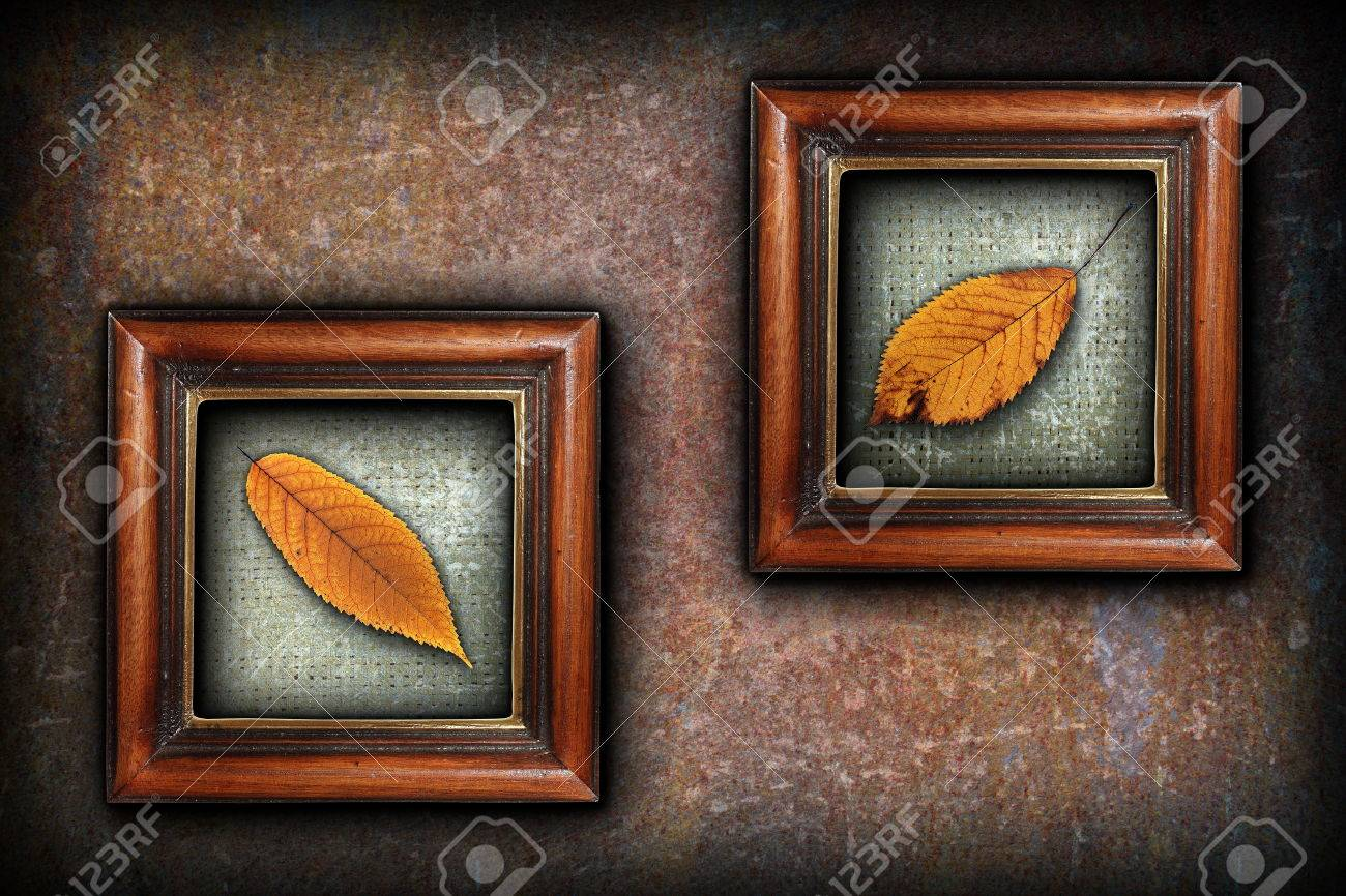 Stock Photo - display of autumn symbols, beautiful golden cherry faded  leaves in old painting wood frames