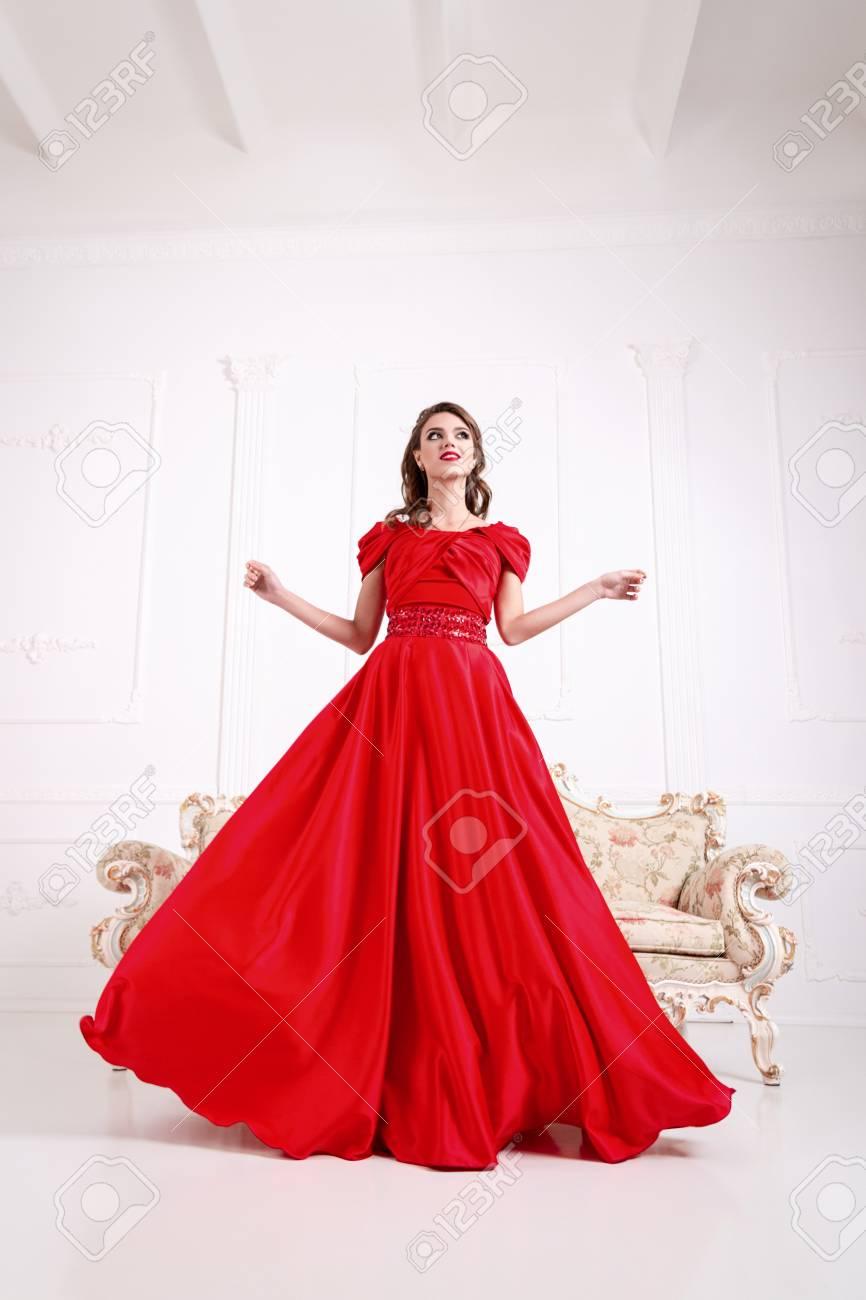 orologio 7fcb3 24f30 Elegante donna in un lungo vestito rosso è in piedi in una stanza bianca,  vestito lampeggiante