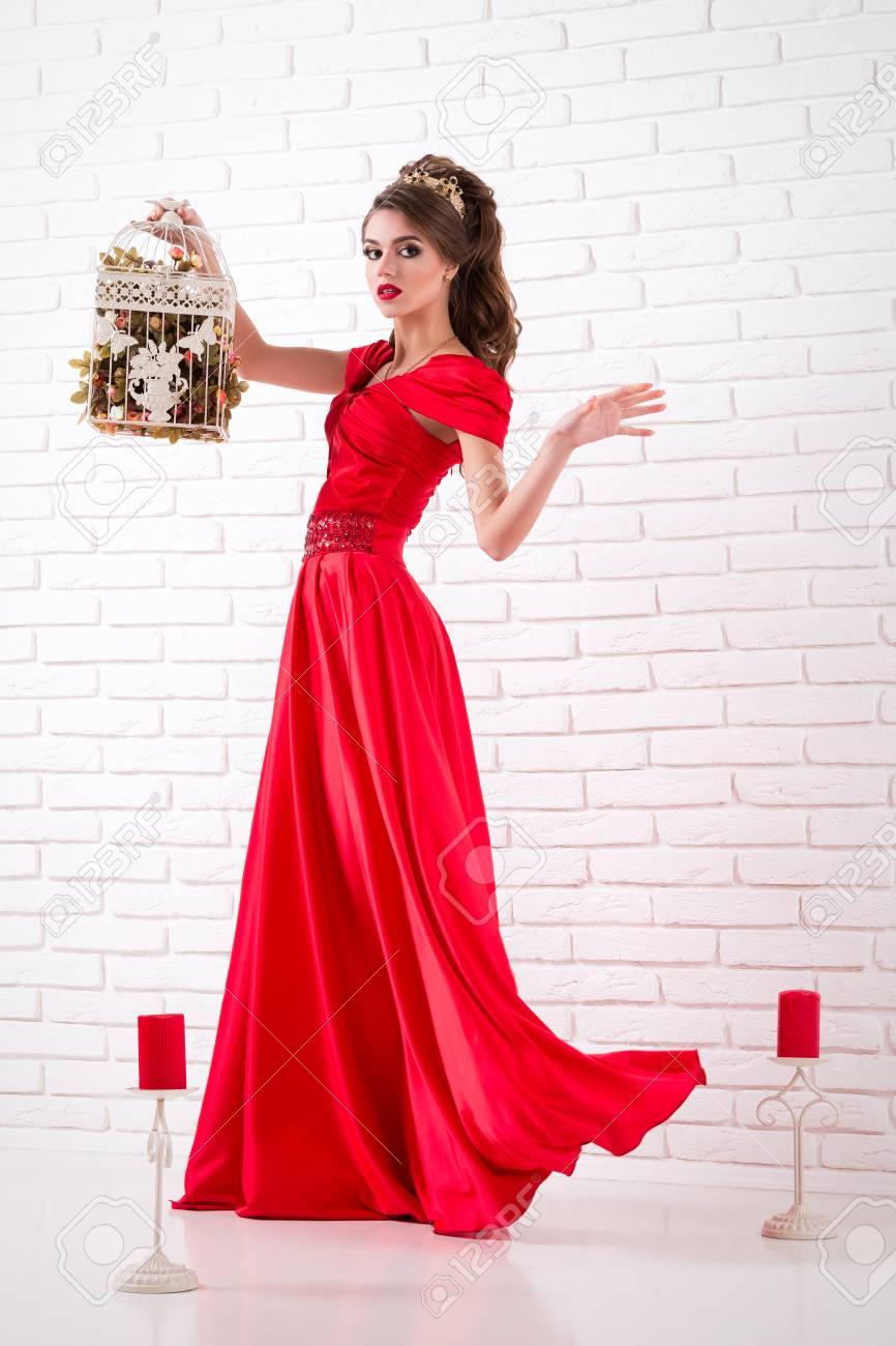 purchase cheap 696c7 13c77 Elegante donna in un lungo abito rosso è in piedi in una stanza bianca e  tiene in gabbia per gli uccelli, vestito lampeggiante