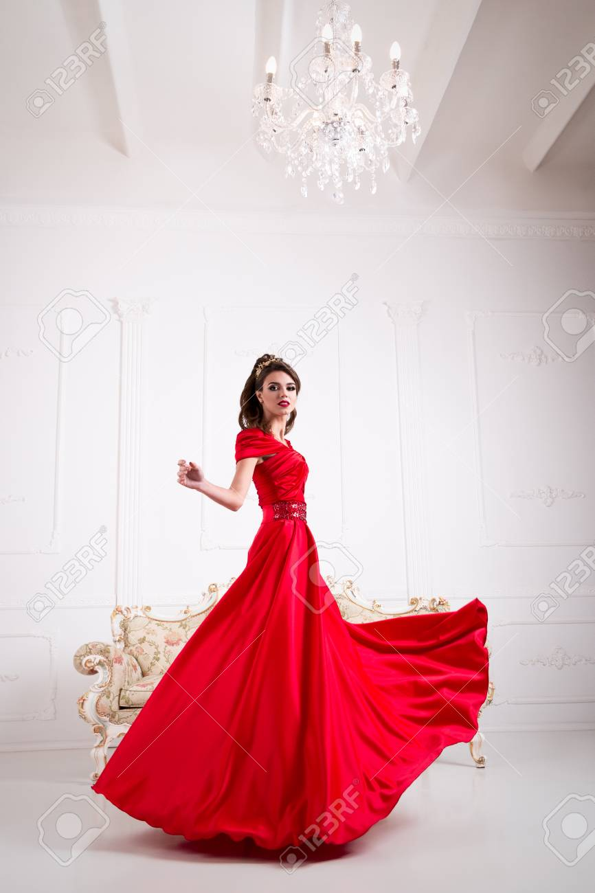 8a980612fbe Banque d images - Femme élégante dans une longue robe rouge est debout dans  une chambre blanche chic