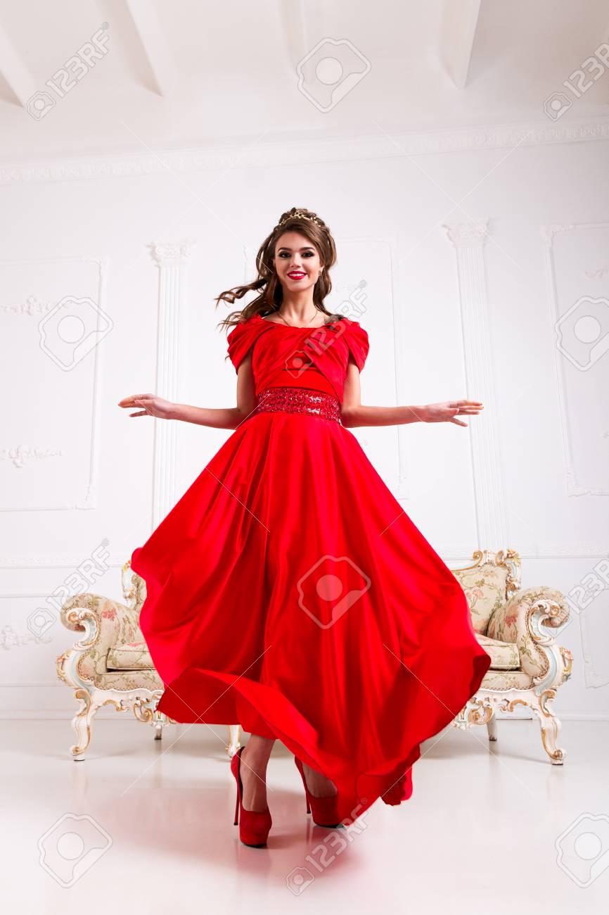 Garantie de satisfaction à 100% gros remise énorme inventaire Femme élégante dans une longue robe rouge est debout dans une pièce  blanche, robe clignotant volant