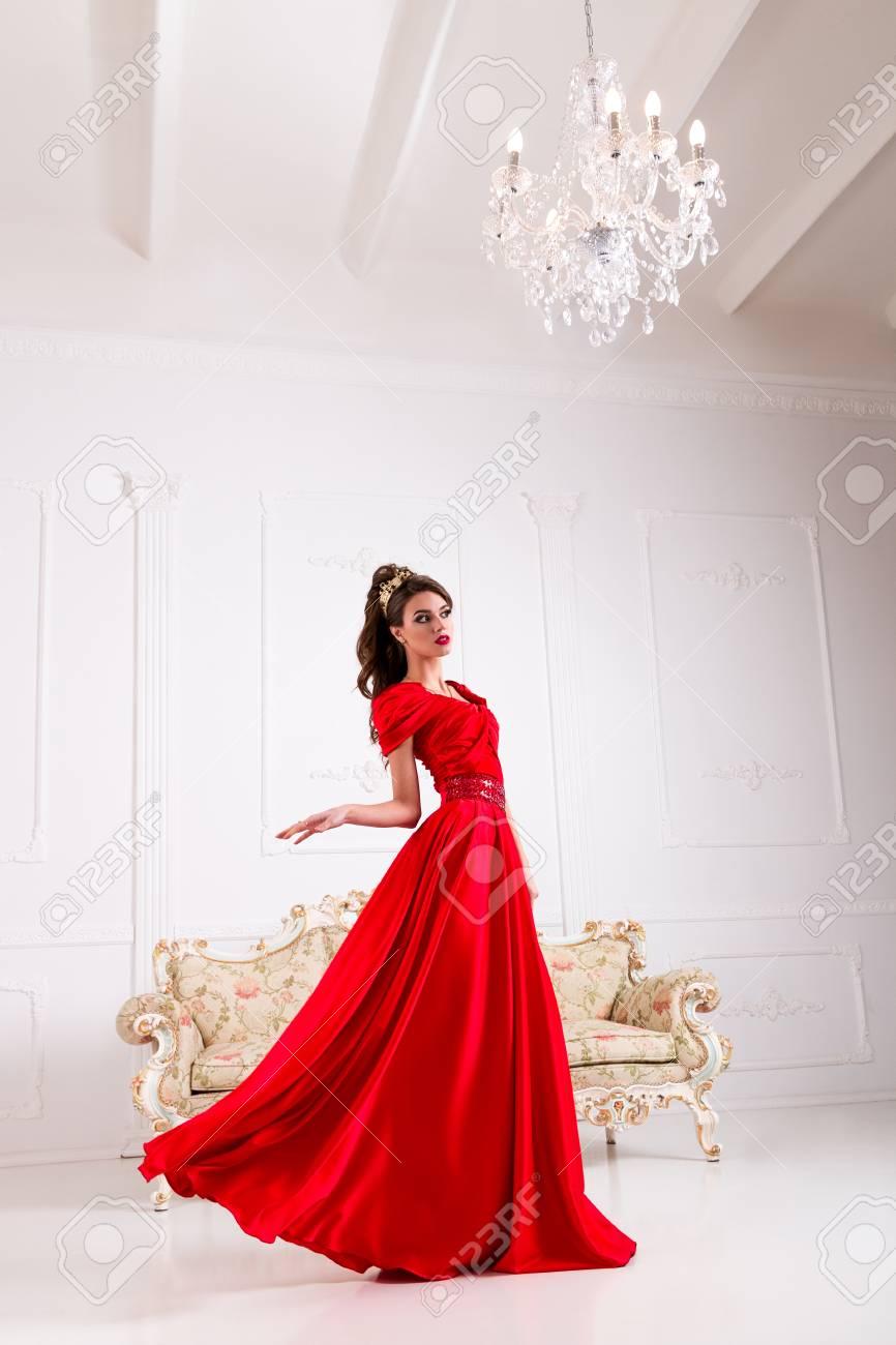 design senza tempo b22c0 fa559 Elegante donna in un lungo abito rosso è in piedi in una stanza bianca,  vestito lampeggiante vortice di volo