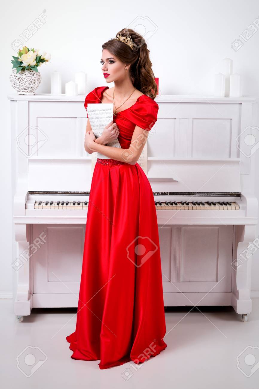 Schöne Elegante Mädchen In Einem Langen Roten Kleid Und Schuhe Hält