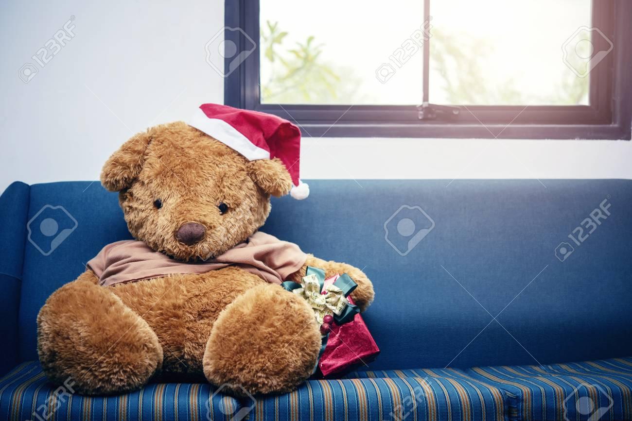 Big Bear Christmas.Big Bear With Christmas Hat And Red Gift Box On Sofa Merry Christmas