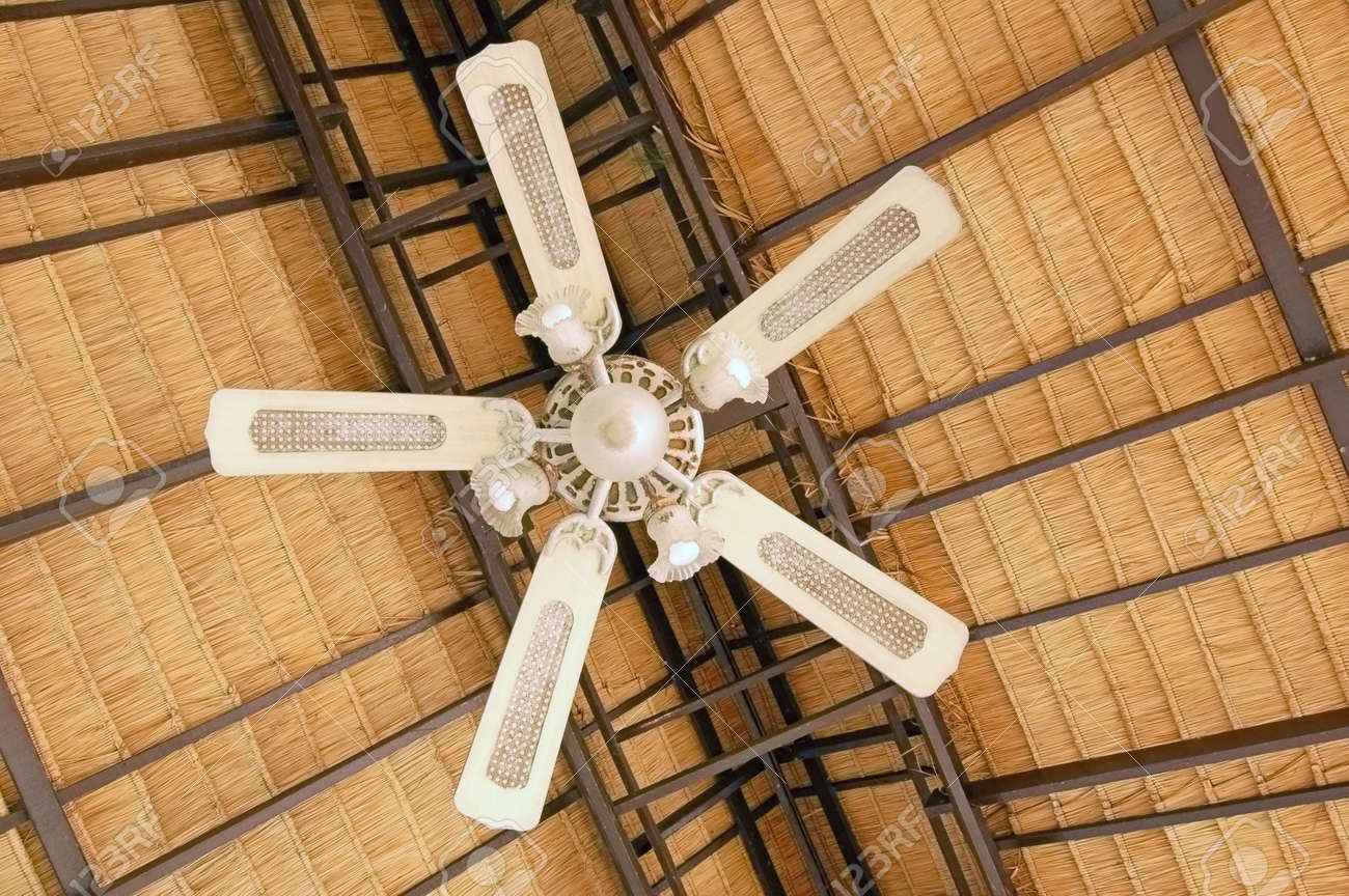 large ceiling fan under a thatched roof stock photo