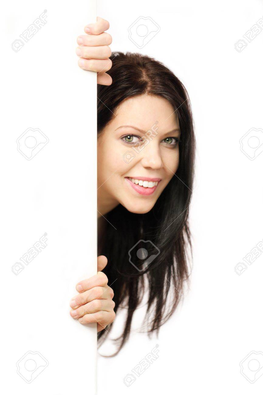 Beautiful young woman with long hair holding white board vertically and  peeping round the corner Stock Photo - 6489393