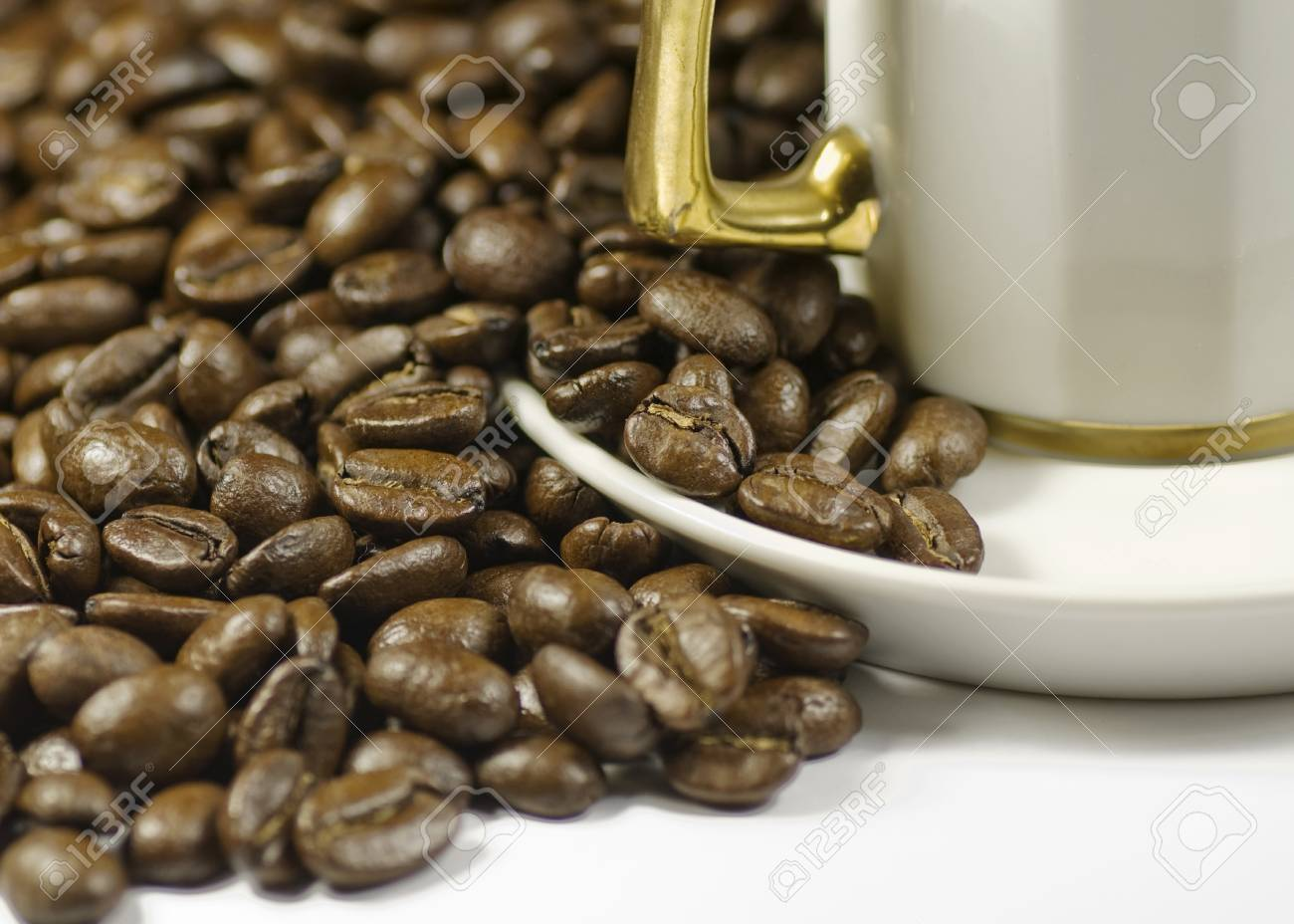 coffe beans by gold handle cup with handle Stock Photo - 8278848