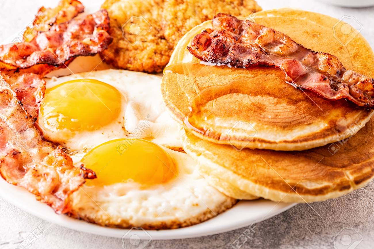 Healthy Full American Breakfast with Eggs Bacon Pancakes and Latkes, selective focus. - 114331673