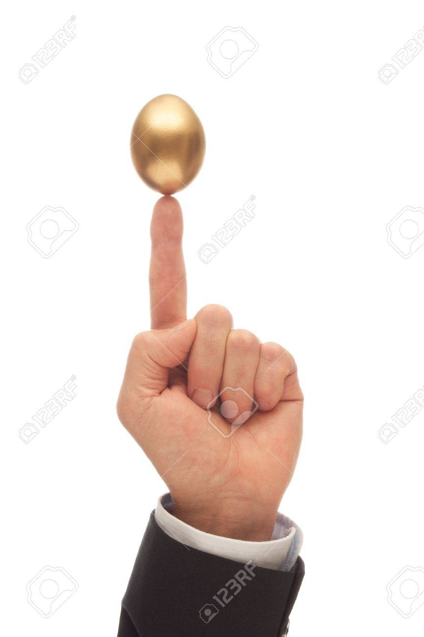 Golden Egg Balanced on the Index Finger of a Man Stock Photo - 21266429