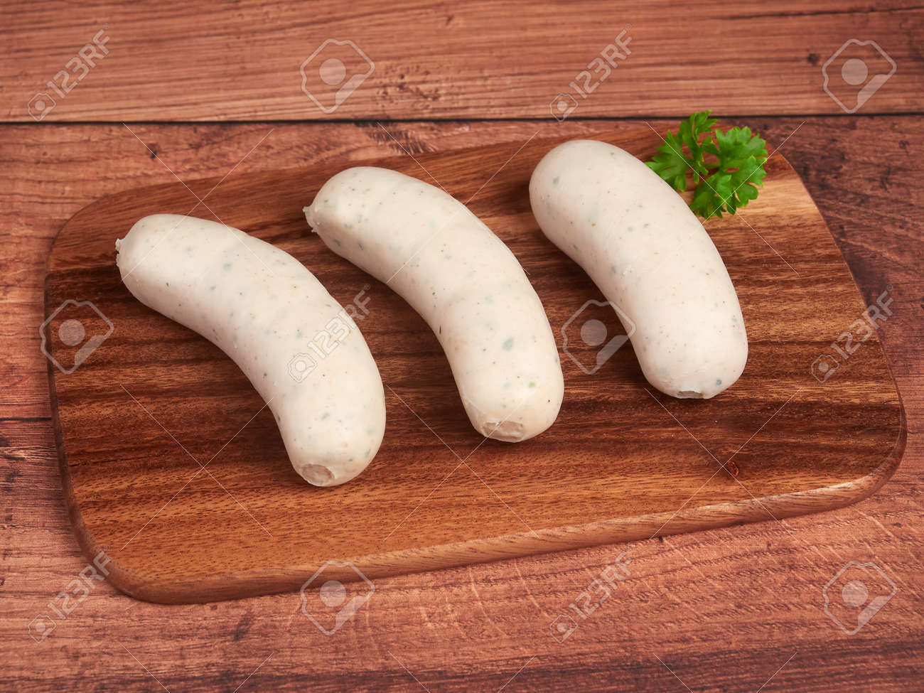Traditional Bavarian white sausages (weisswurst) on a wooden board - 156154217