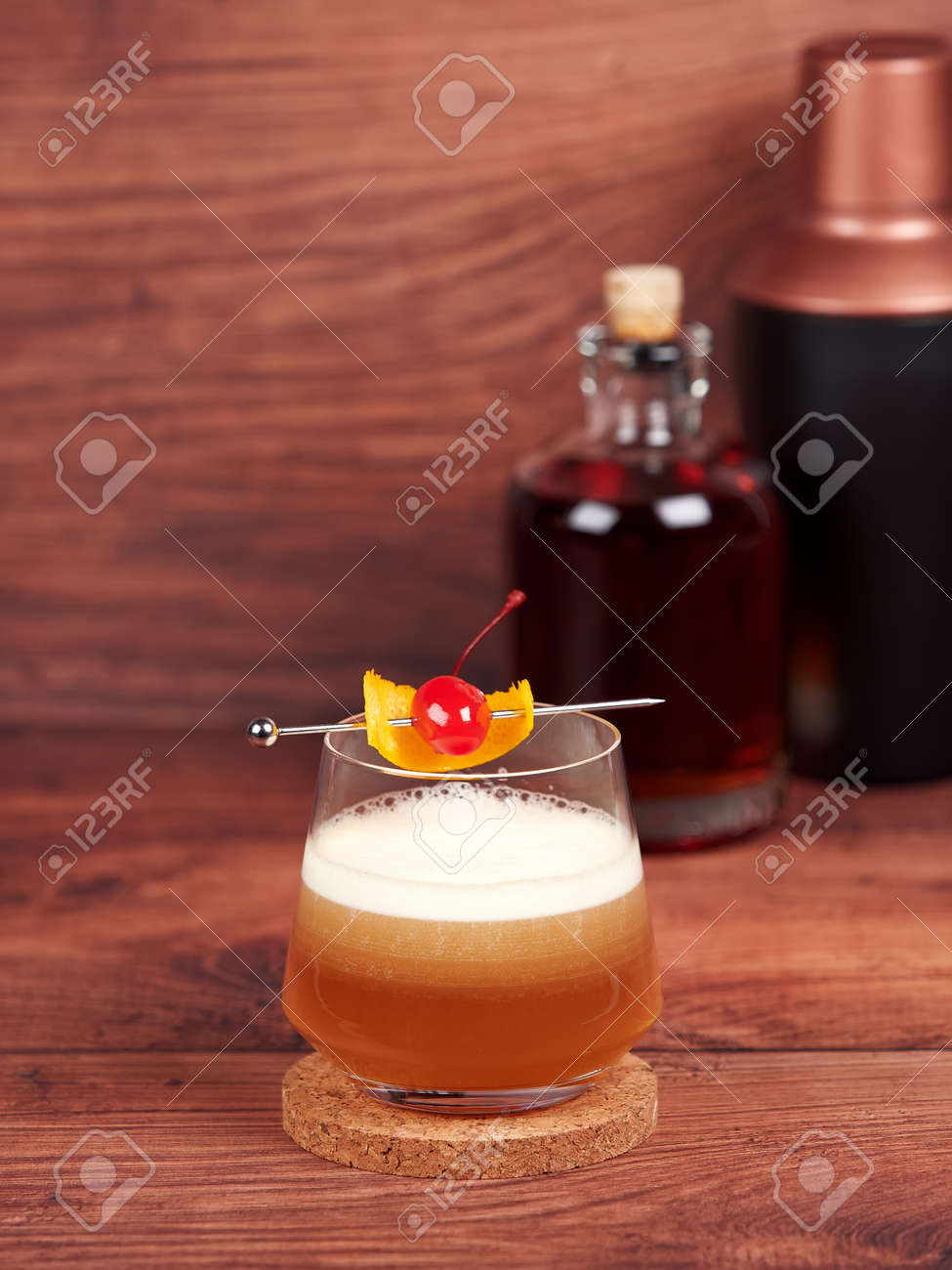 Amaretto sour: a cocktail made with amaretto liqueur, lemon juice, simple syrup and egg white, and topped with a cherry and orange - 157025443