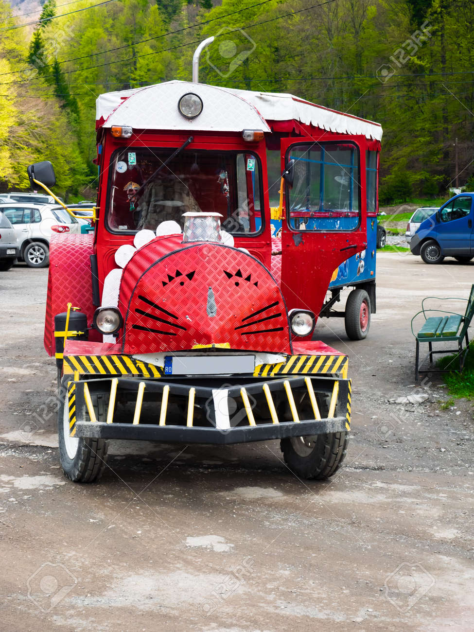 Busteni, Romania - May 3, 2014: A red tractor with a trailer acts as a means of transportation between Busteni Train Station and Gura Diham chalet - 164519673