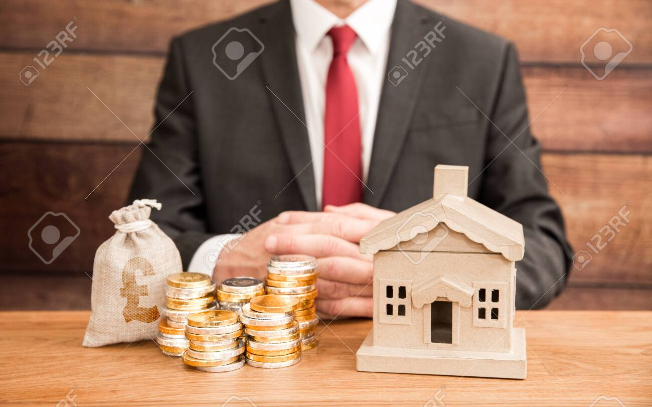 A housing concept of the cost and price of homes with a real estate agent or mortgage broker sitting with a property and money to represent fees, mortgage and house prices. - 155516544