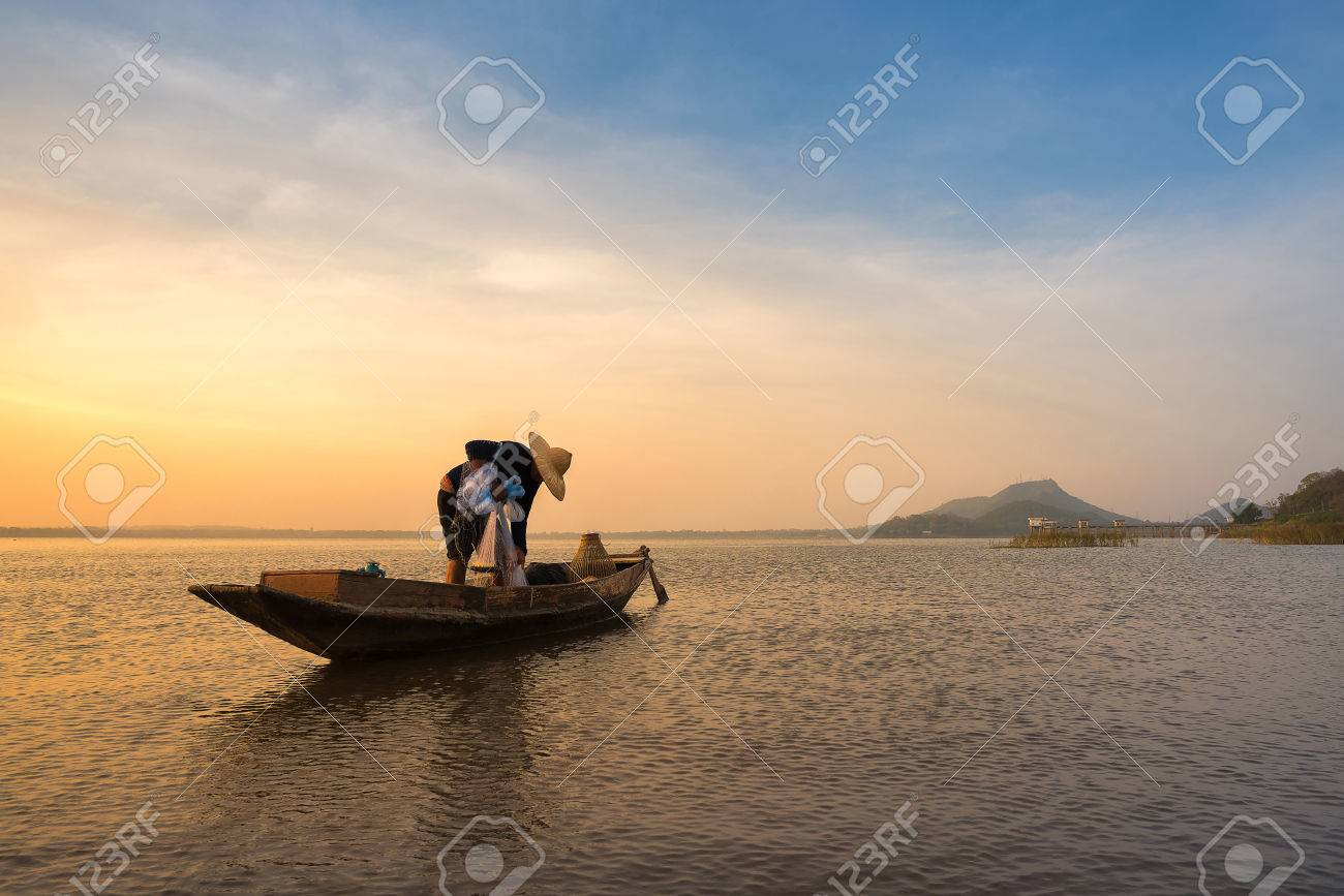 Asian fisherman on wooden boat preparing a net for catching freshwater fish in nature river in the early morning before sunrise - 54804085