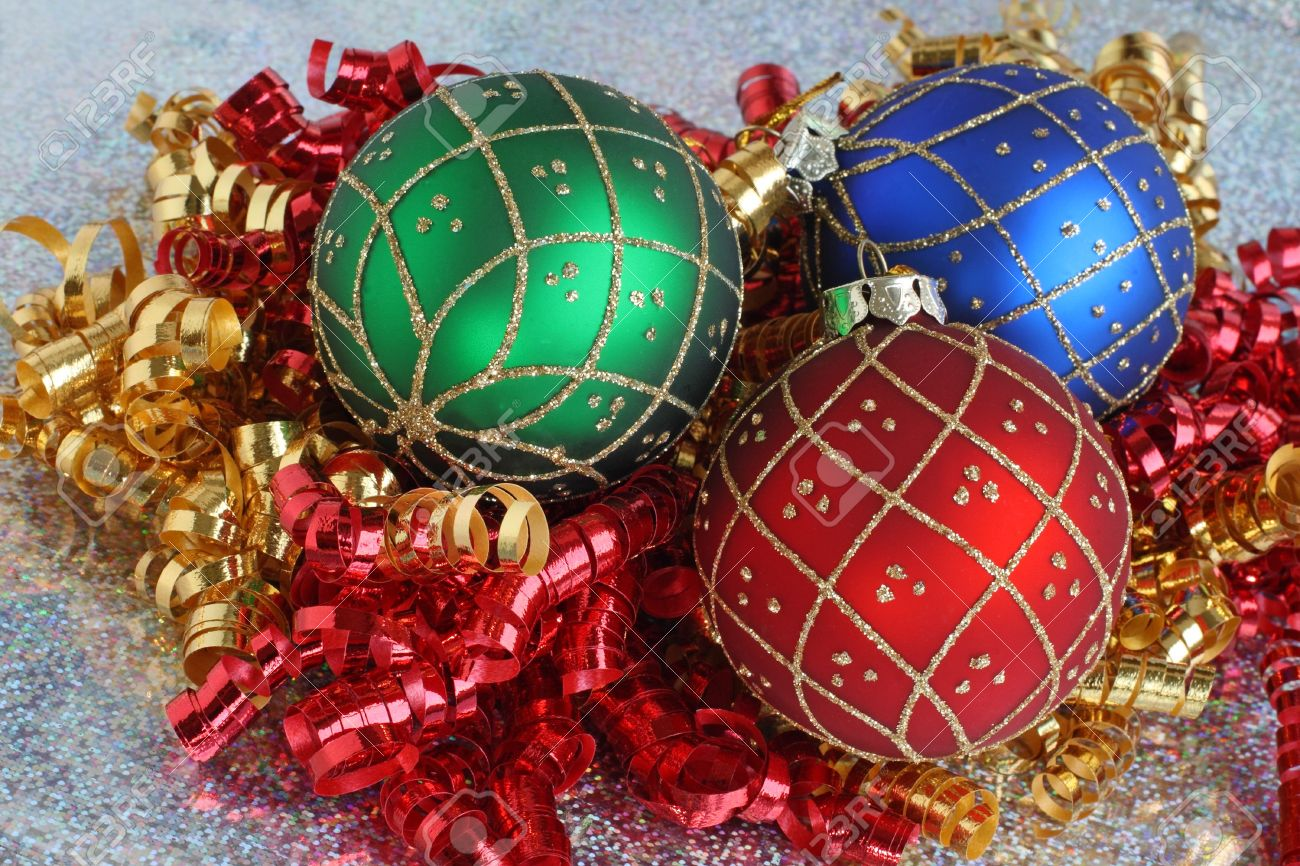 Three Glittery Christmas Ornaments And Curled Ribbon On Sparkling