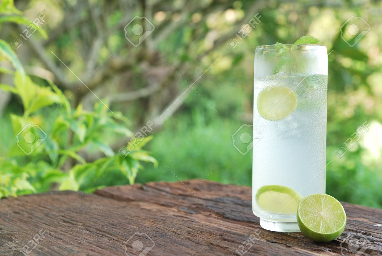 Full glass of fresh cool tonic with lime fruits isolated on wood table Stock Photo - 28387931