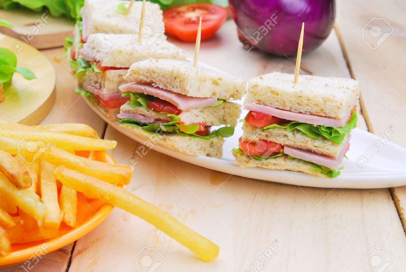 Club Sandwich with Cheese, Pickled Cucumber, Tomato and ham. Garnished with French Fries - 30635456