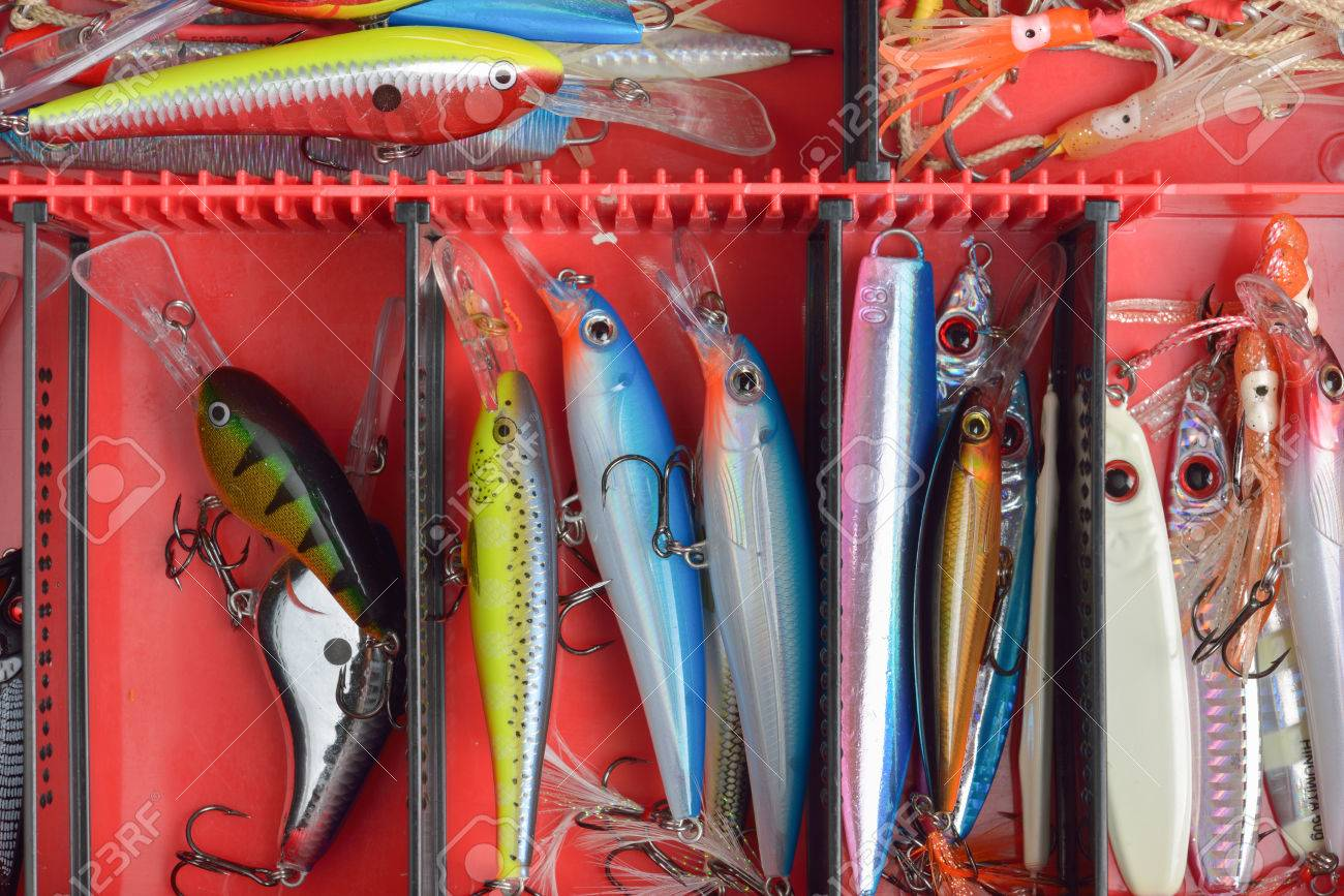 Colorful Fishing Lures on plastic box desk different fishing baits The fishing equipment. - 53242112