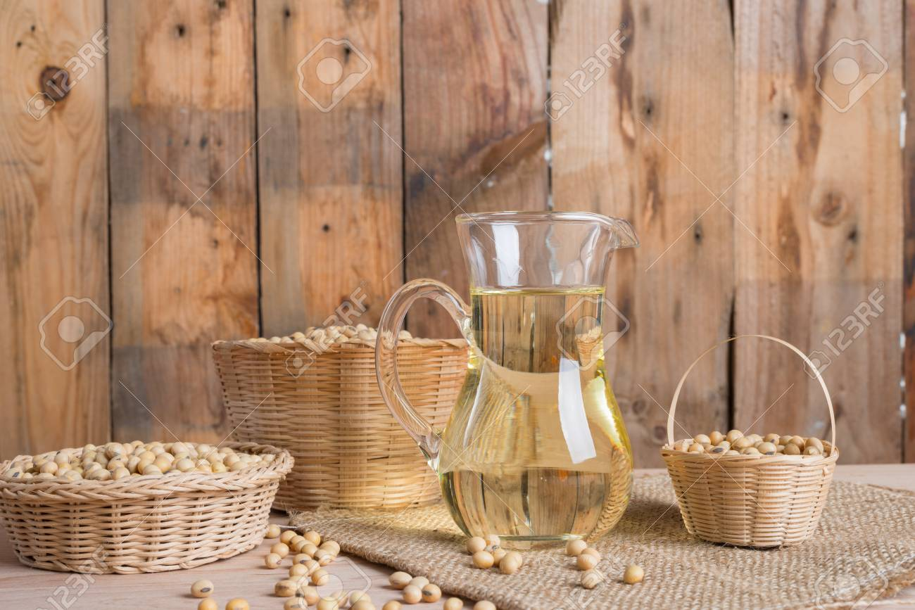 Soybean in basket and soybean oil in jar on wooden background - 87105963
