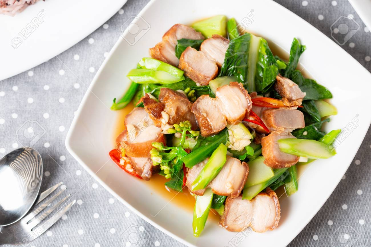 Crispy Pork Belly Stir Fry With Chinese Kale in white plate