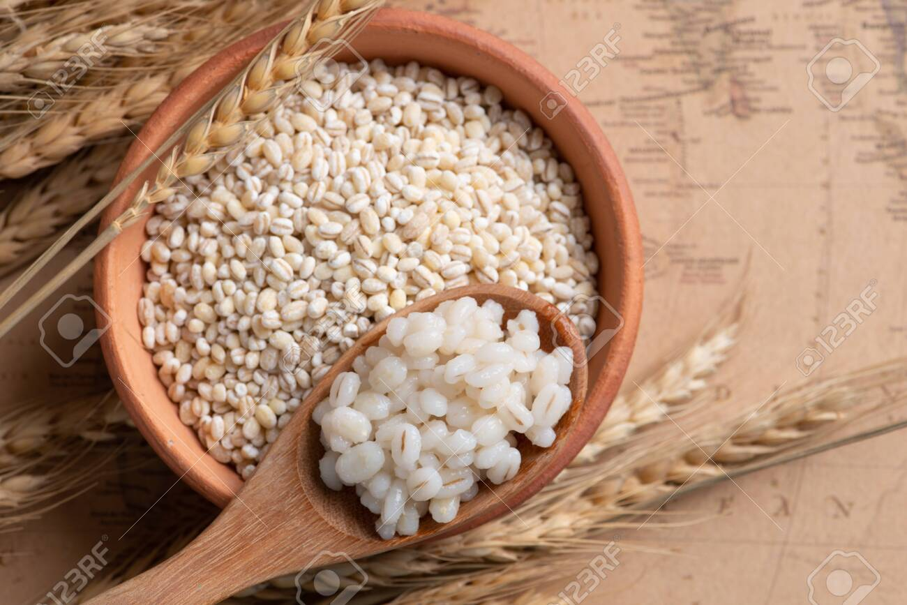 Cooked peeled barley grains in wooden bowl on wooden table - 129276945