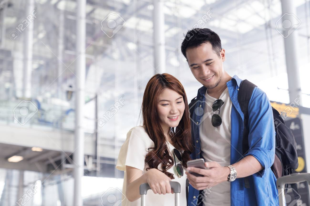 Couple asian student traveler looking or find for flight in smartphone at airport terminal. Check-in by mobile. Teenager are traveling concept. - 91657582