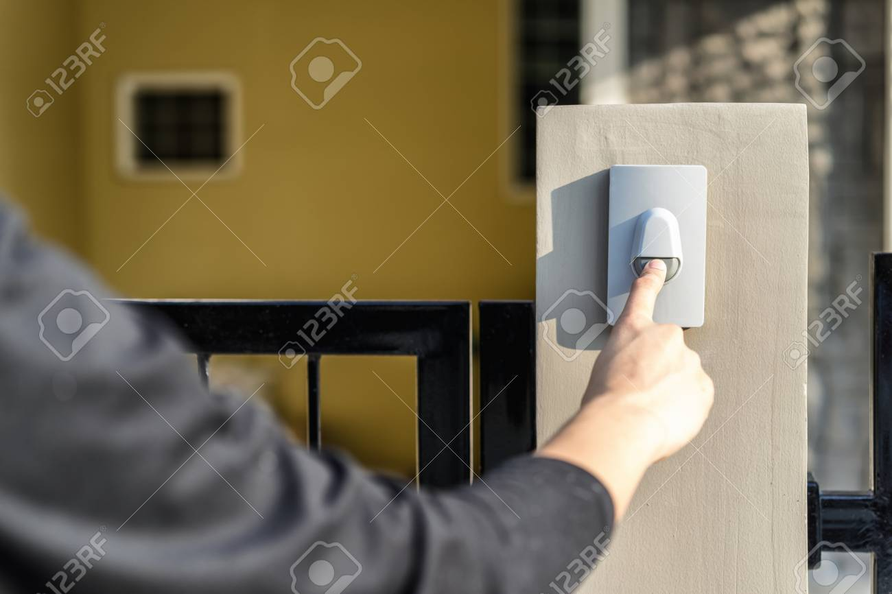 Man's hand pressing a doorbell button with sunlight. Close up hand and finger visiter ringing buzzer doorbell. Guest press bell behind front door home. - 96739883