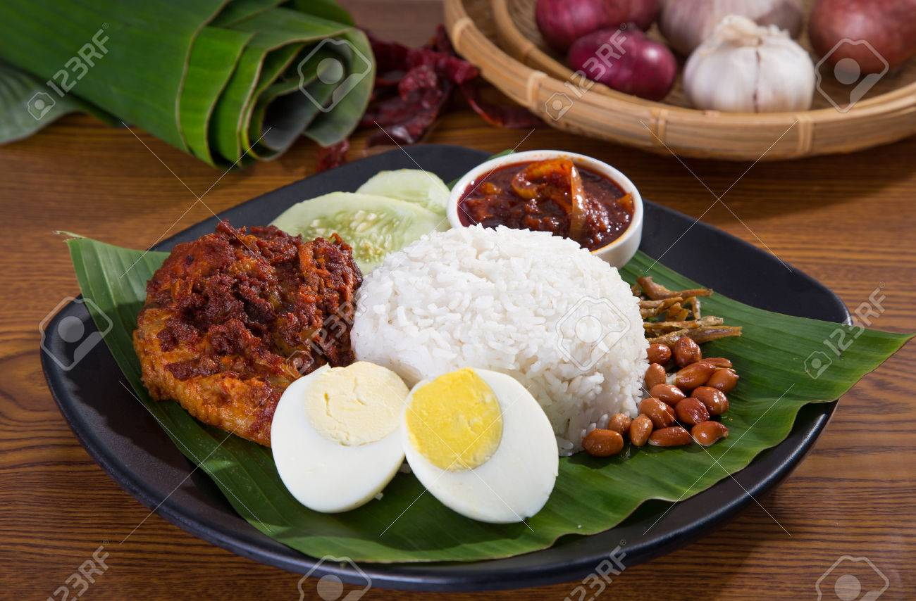 nasi lemak, a traditional malay curry paste rice dish served on a banana leaf - 54513282