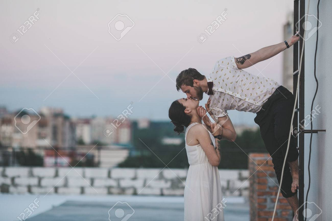 beautiful couple together on the roof of a tall building - 39036650