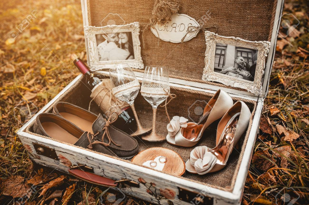 suitcase with different wedding accessories in the background leaves - 39952306