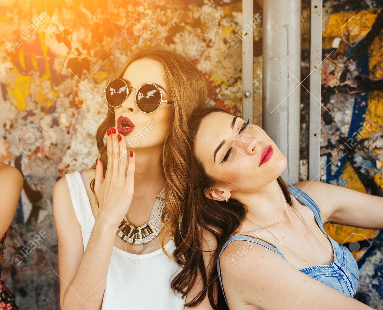 two young beautiful girls rest at a bus stop stock photo picture